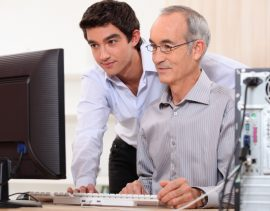 younger and older man looking at computer